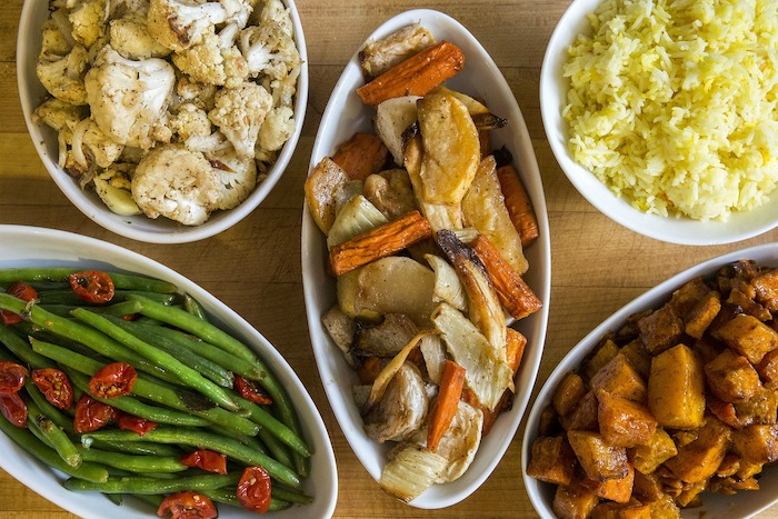 thanksgiving side dishes wooden surface five white plates on it with different dishes beans rice cauliflower potatoes carrots