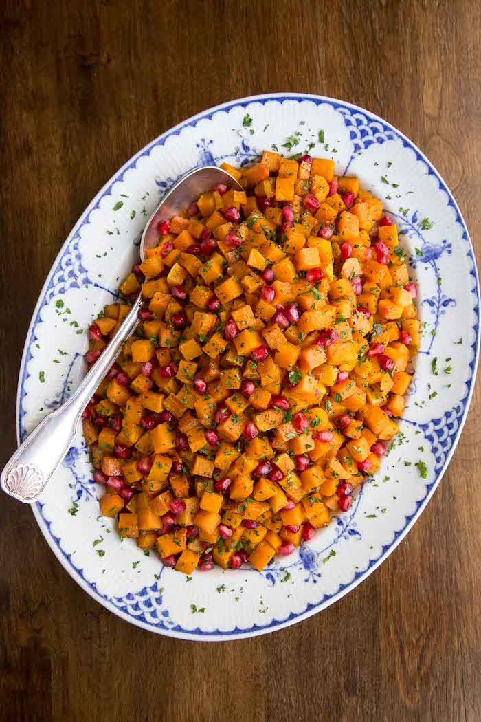 thanksgiving vegetable side dishes roasted carrots with pomegranate seeds in blue and white plate spoon on the side