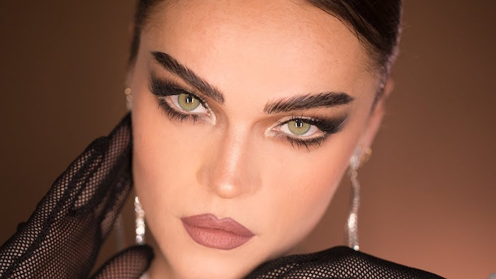 thick eyebrows on green eyed woman with brown hair winged eyeliner for hooded eyes nude lipstick