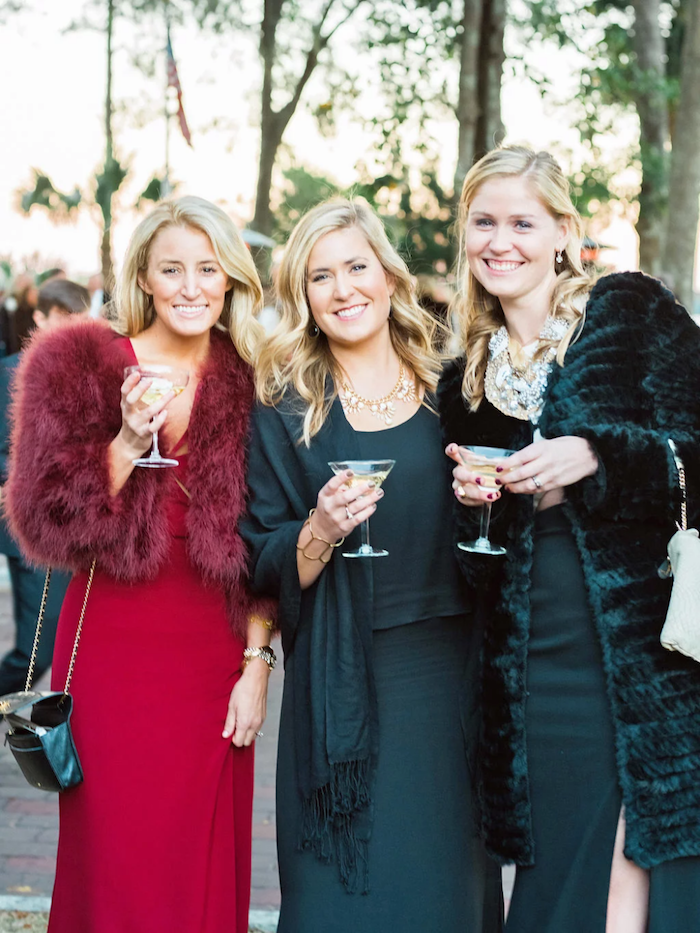 three women wearing olive green and red dresses formal dresses for weddings wearing furry coats in green and red