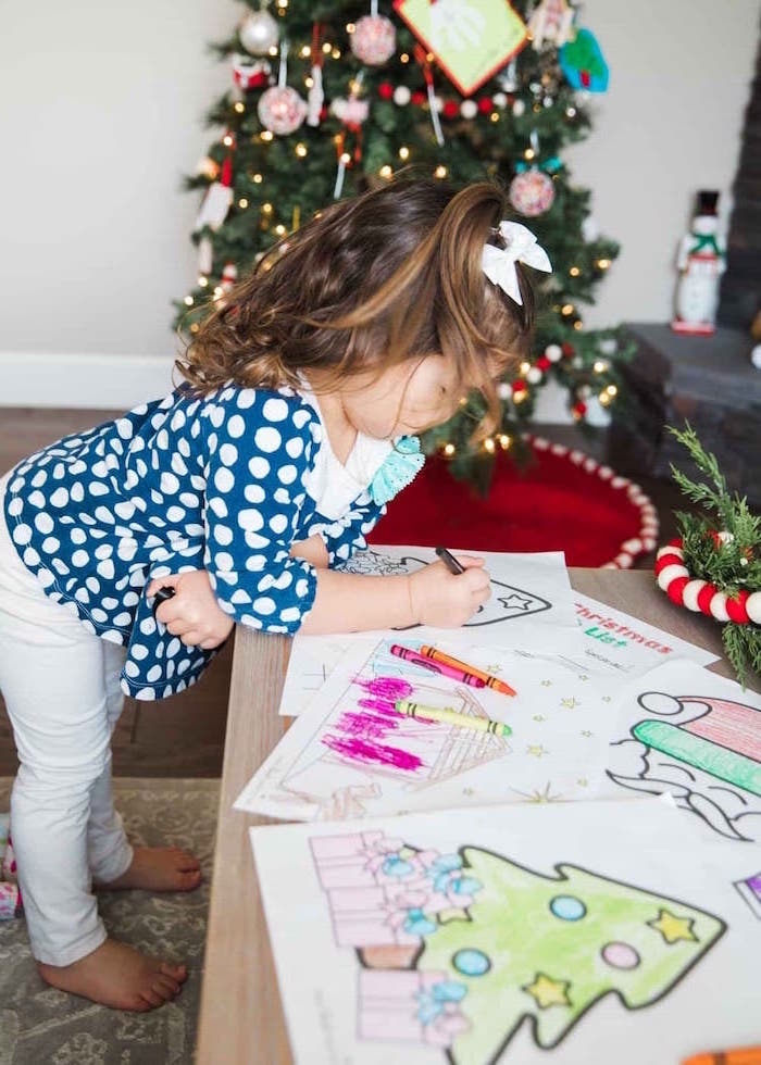toddler coloring on wooden table wearing white pants blue blouse with white dots coloring sheets for kids christmas tree in the background