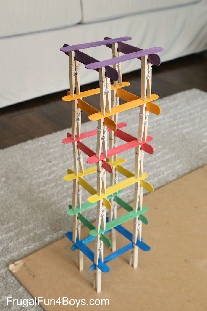 tower built out of popsicle sticks in purple orange red yellow green blue clothespins fun things to do with kids
