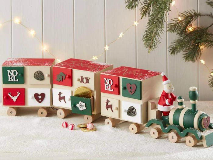 toy train with three wooden carriages with small boxes with candy inside fun advent calendars decorated in green and red