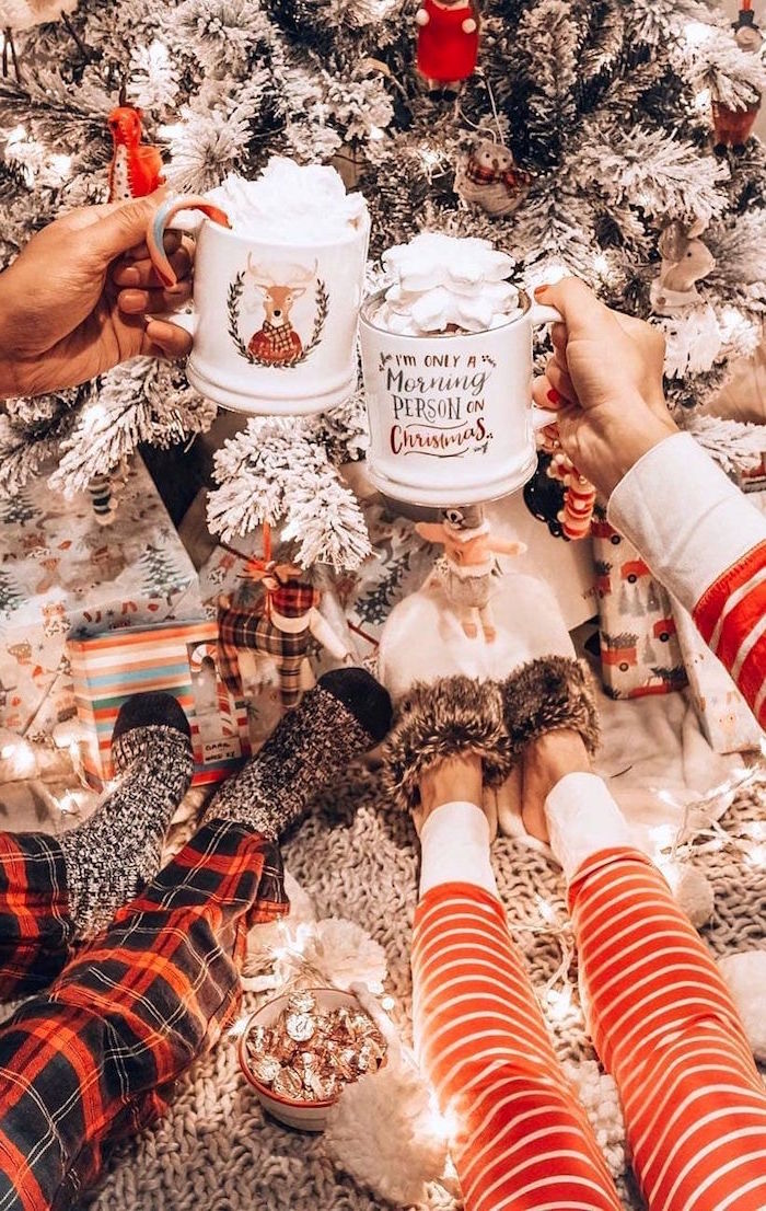 two people standing next to christmas tree wearing pjs holidng christmas mugs merry christmas wallpaper