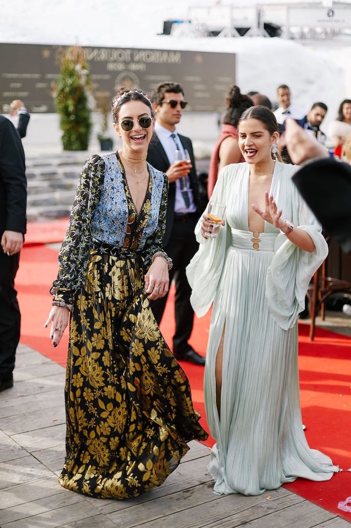 two women walking on red carpet winter wedding guest dresses both wearing dresses with long sleeves deep necklines