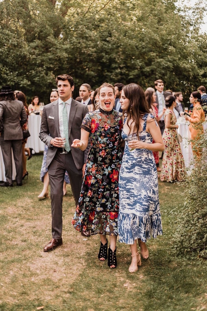 two women wearing floral dresses walking down a pathway surrounded by trees affordable wedding guest dresses