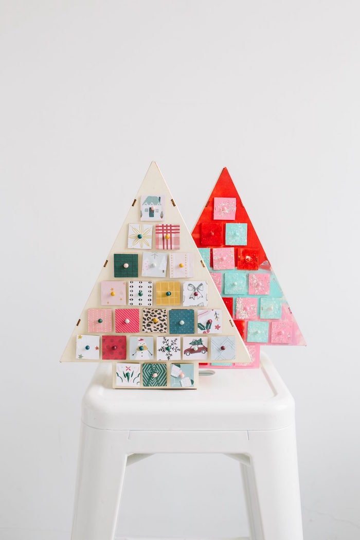 two wood christmas trees placed on white side table advent calendar little boxes attached to them decorated in different colors