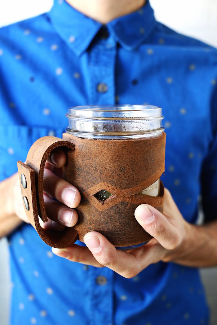 unique gifts for dad man wearing blue shirt holding a mug with leather jar sleeve around it made from brown leather