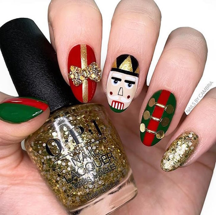 white background christmas nail designs 2020 nutcracker inspired nail design with gold glitter red green black white nail polish