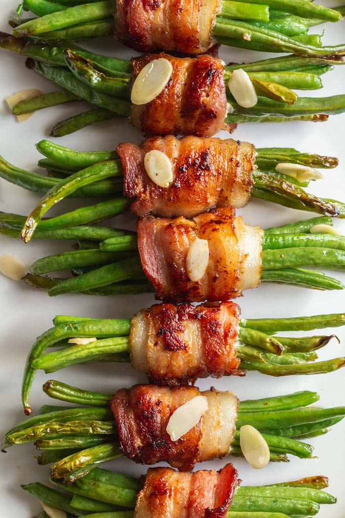 white plate filled with bacon wrapped green beans christmas food ideas garnished with silvered almonds
