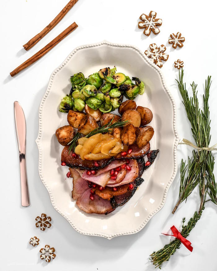 white plate with slices of ham brussels sprouts potatoes placed on white surface christmas dinner 2020 knife rosemary branches cinnamon sticks snowflake cookies on the side