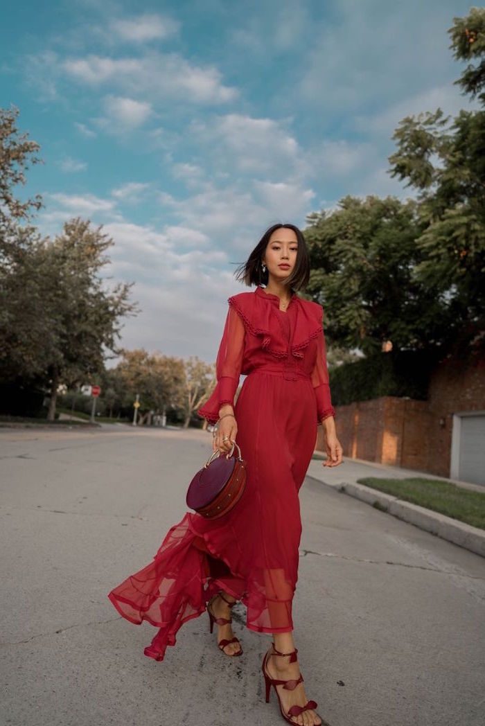 winter wedding guest dresses woman walking down the street wearin long red dress with long sleeves red sandals