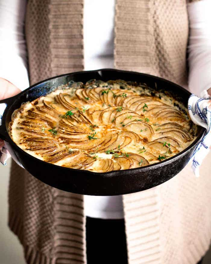 woman holding black skillet best thanksgiving side dishes creamy potatoes au gratin inside