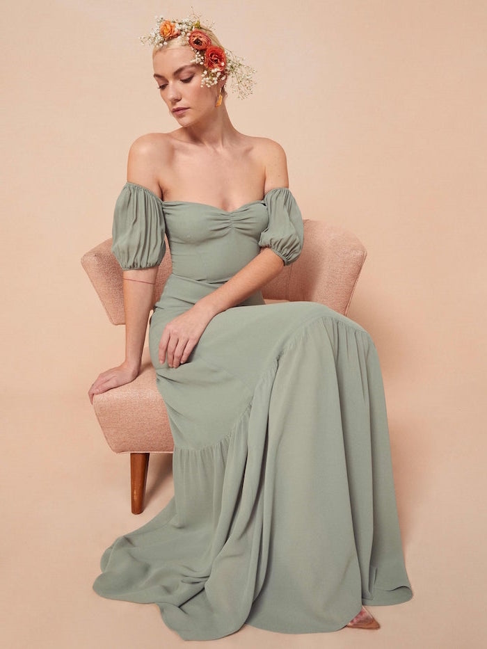 woman sitting on pink chair semi formal dresses for wedding wearing long green off the shoulder dress