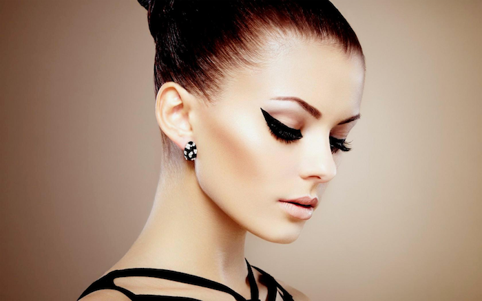 woman wearing black dress with black hair in high bun cat eye eyeliner with black eyeliner