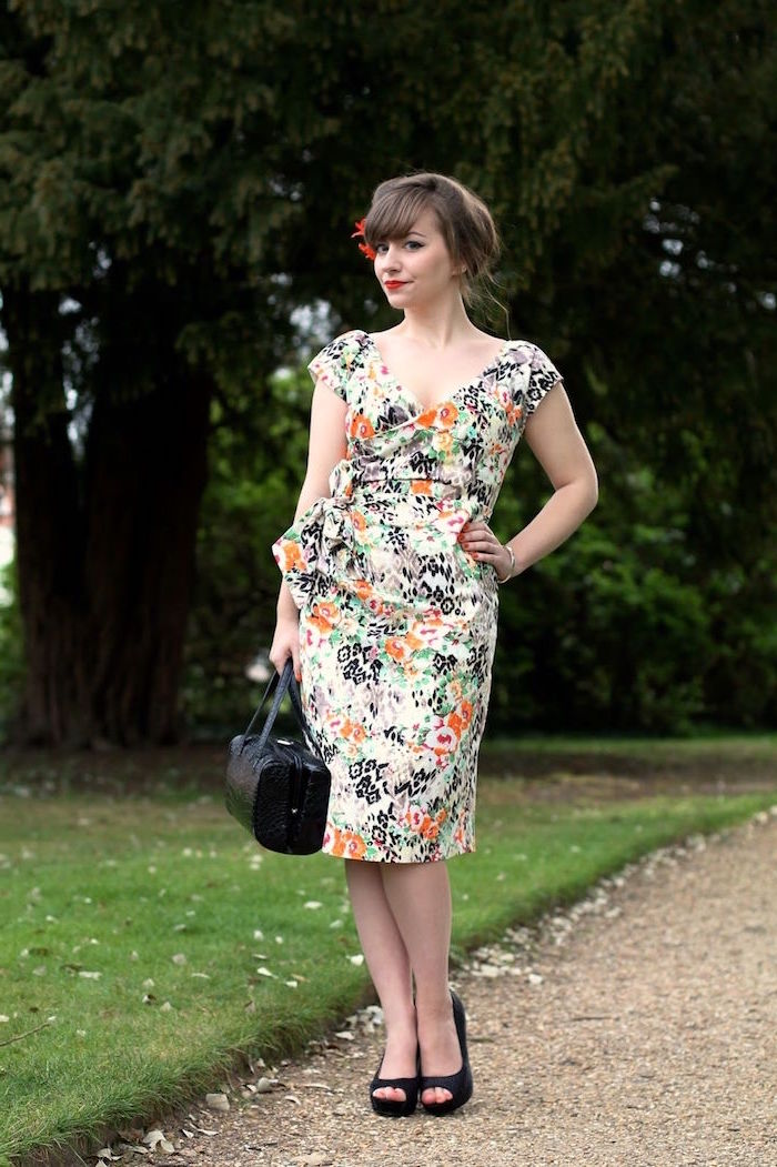 woman wearing floral dress black shows and bag elegant dresses for wedding guests brunette hair in high updo