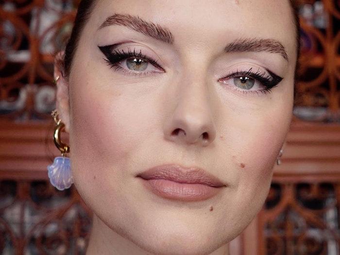 woman with green eyes thick eyebrows brown hair cat eye eyeliner with black eyeliner seashell earrings