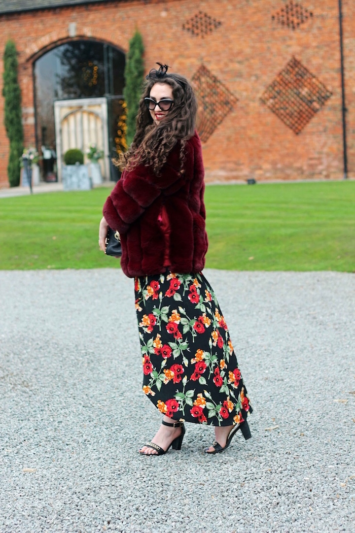 womens wedding guest dresses woman with long black curly hair long floral dress red furry coat black sandals