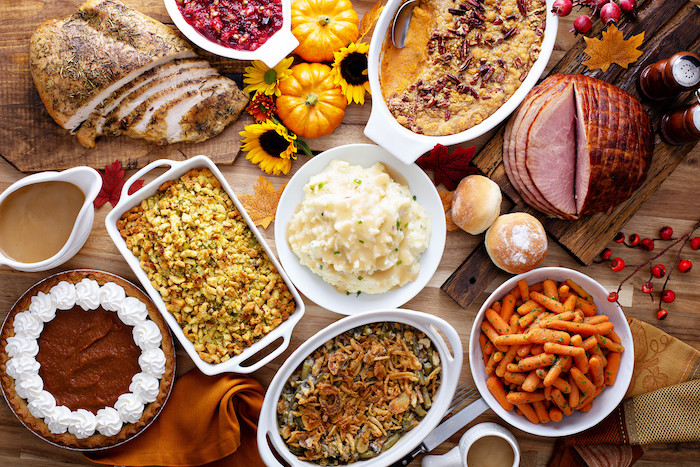wooden table full of different thanksgiving side dishes in white plates casseroles mashed potatoes ham carrots casseroles