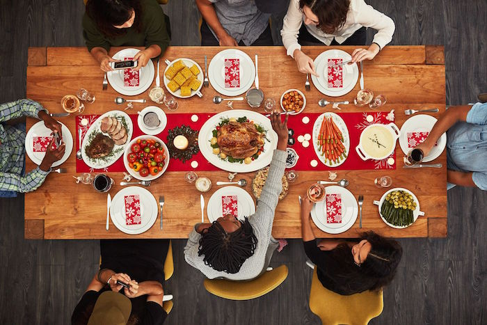 wooden table with red table runner christmas eve dinner ideas eight people sitting around it white plates and different dishes
