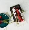 yule log christmas dessert placed on black and white marble board easy christmas dinner ideas decorated with rosemary and cranberries
