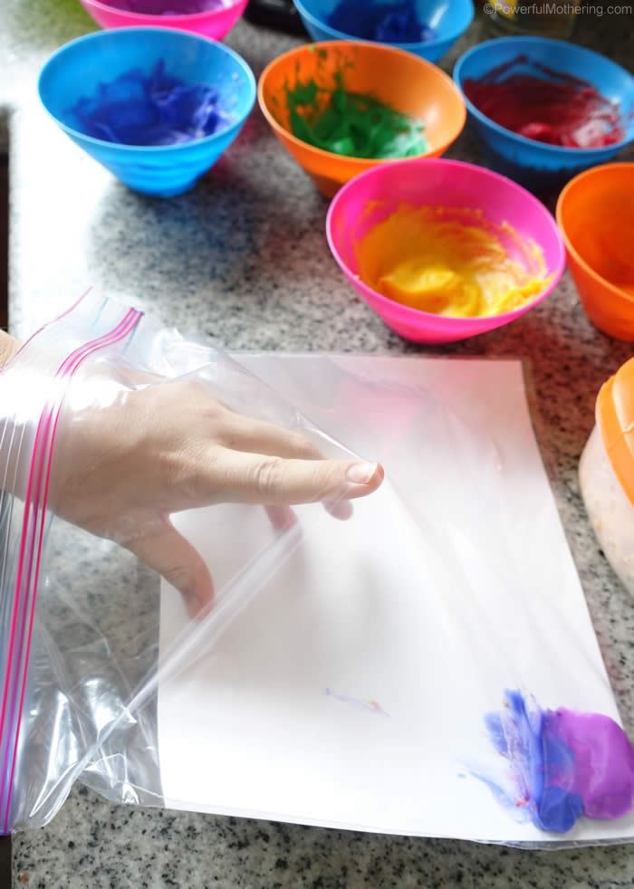 ziploc bag with purple and blue paint inside things to do with kids at home lots of bowls next to it with paint in different colors