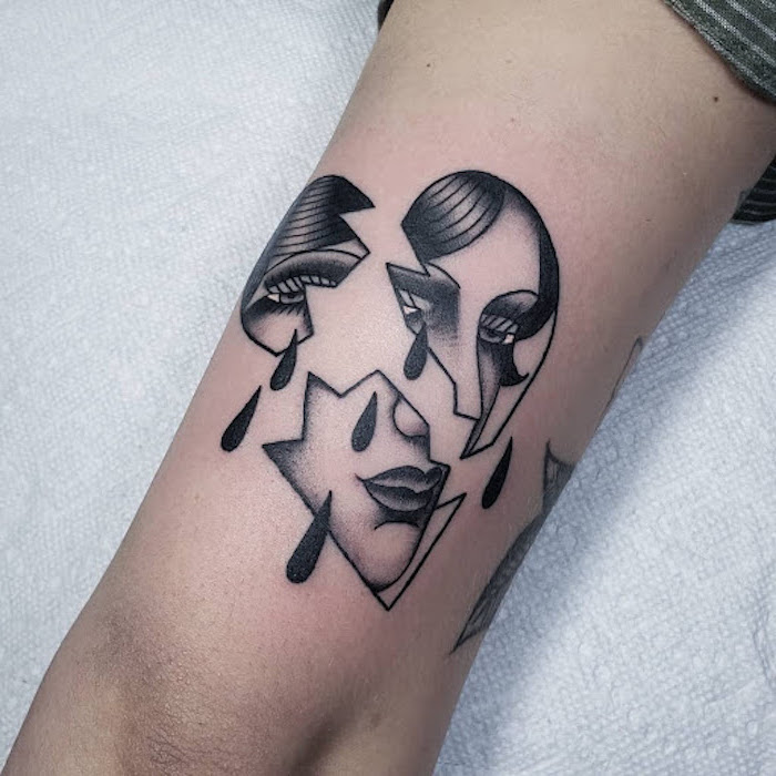back of arm tattoo above the elbow heart tattoo on hand heart with female face drawn inside broken into three pieces