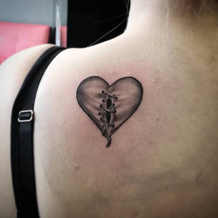 back tattoo of heart with black outlines gray shadows heart tattoo on hand held together with bandages