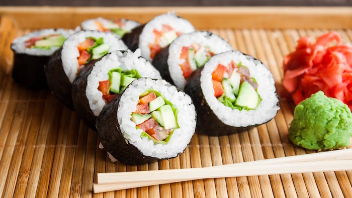 bamboo mat with sushi rolls arrranged on them shrimp tempura roll wooden chopsticks wasabi on the side