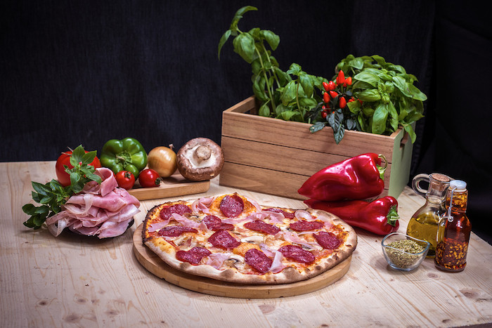basil in wooden crate placed on wooden table homemade pizza dough salami pizza with mushrooms placed on wooden cutting board