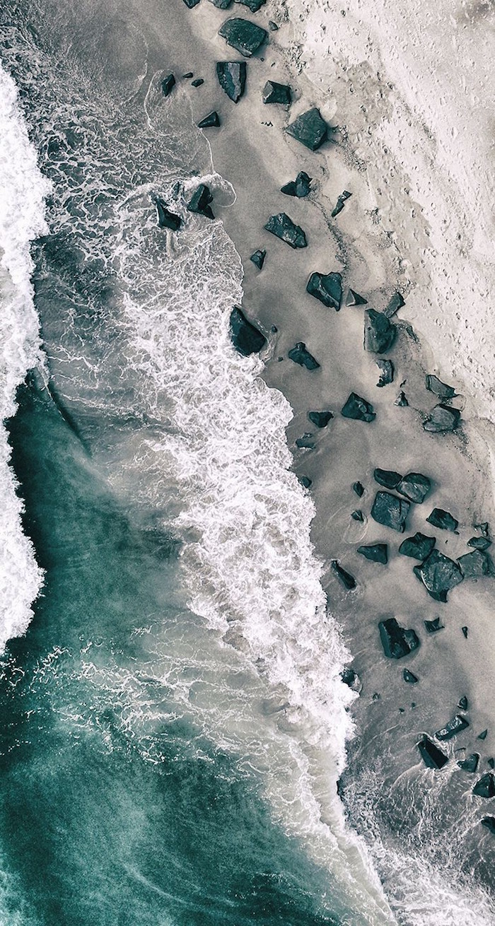 beach photographed from above minimalist phone wallpaper waves crashing into the rocks