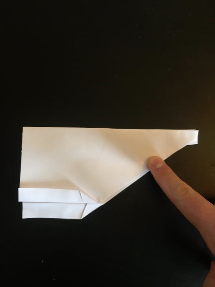 best paper airplane design black background a white piece of paper folded into a plane