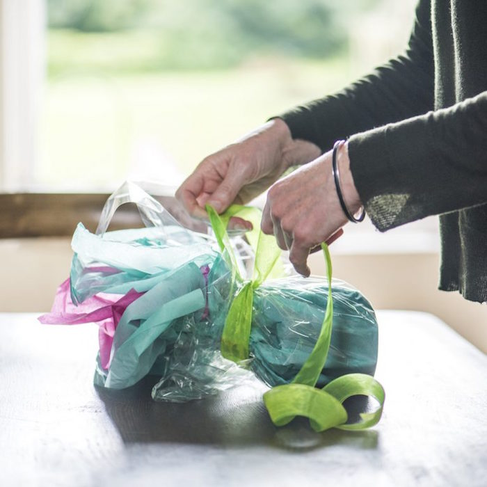 best way to wrap presents ceramic mug wrapped in turquoise pink tissue paper tied with green tulle ribbon