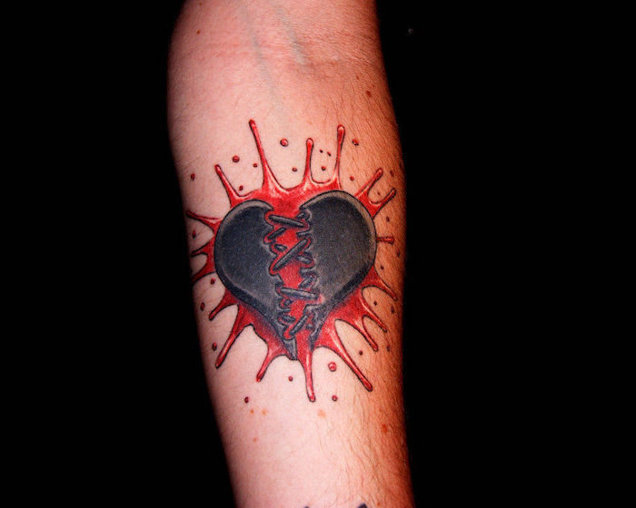 black heart cracked in the middle heart tattoo on hand splash of red blood as background forearm tattoo