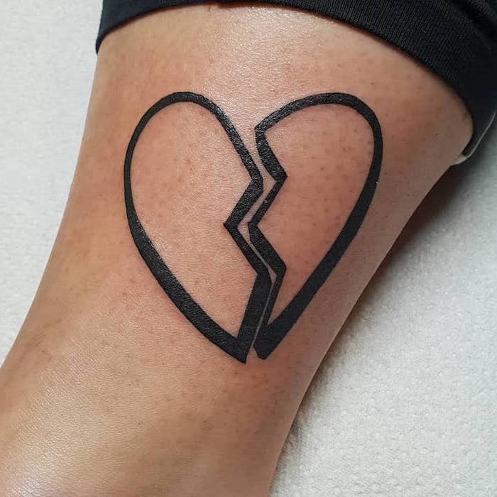 black putline of two pieces of a heart separated in the middle heart tattoos with names inside the leg tattoo