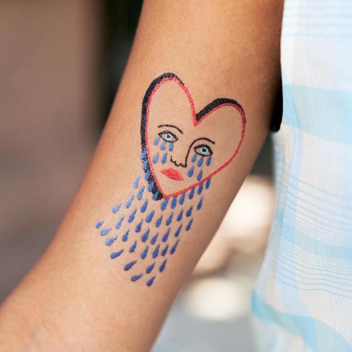 blue tears falling out of heart with red and black outlines heart tattoo on chest blue eyes red lips nose