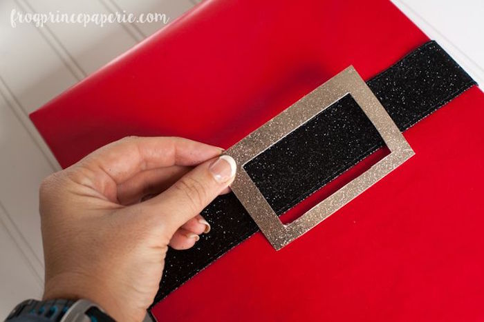box wrapped with red wrapping paper gift packing ideas black glitter ribbon with gold glitter belt buckle to represent santa