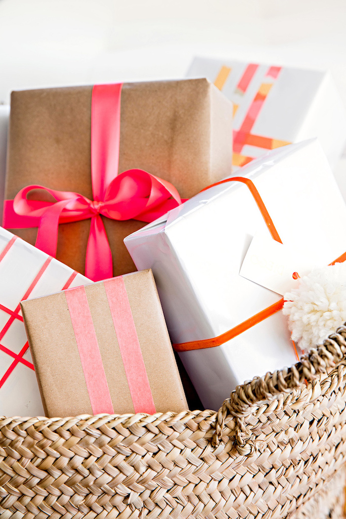 bunch of gifts placed in a basket how to wrap a gift wrapped in white and brown paper tied with red orange pink bows