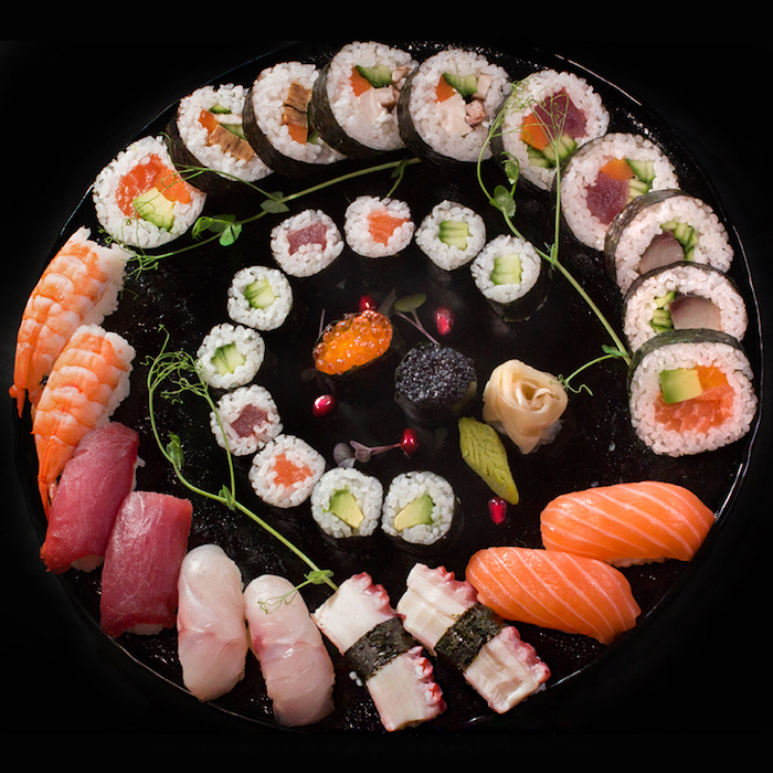 california roll recipe large round black tray with different types of sushi arranged on it in circle