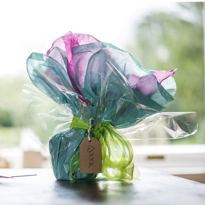ceramic mug being wrapped in pink and turquoise tissue paper diagonal gift wrapping tied with green tulle ribbon