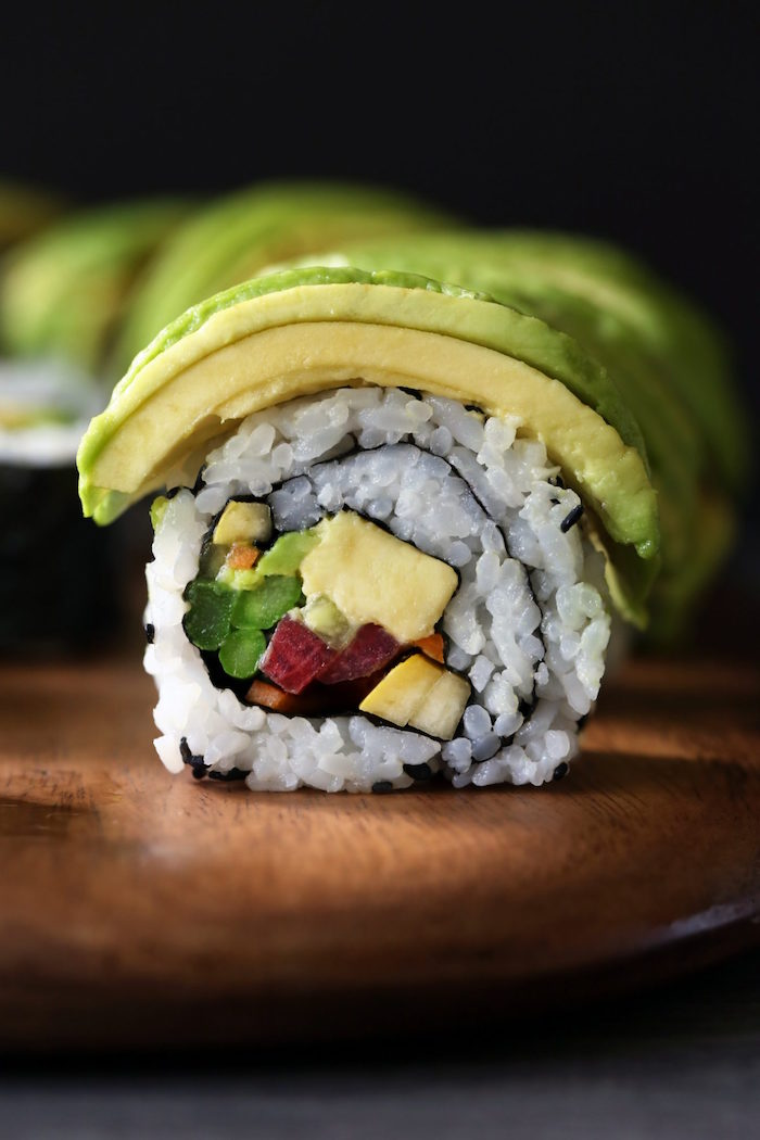 close up photo of vegetable sushi rolls with rice avocado cucumbers how to make sushi at home placed on wooden cutting board