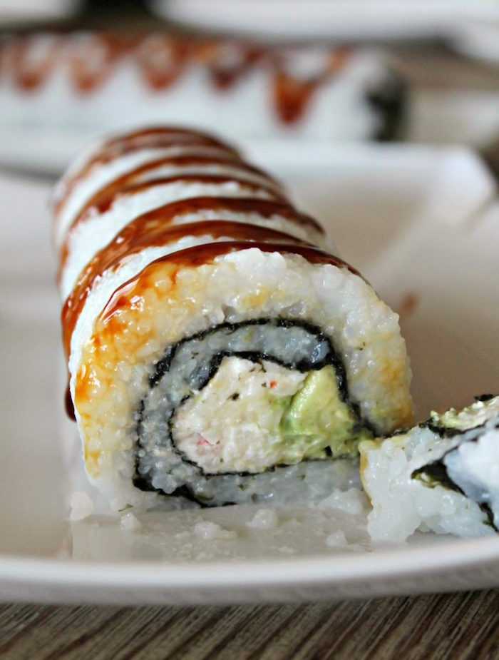 crab roll with avocado rice dragon roll sushi placed on white plate drizzled with soy sauce