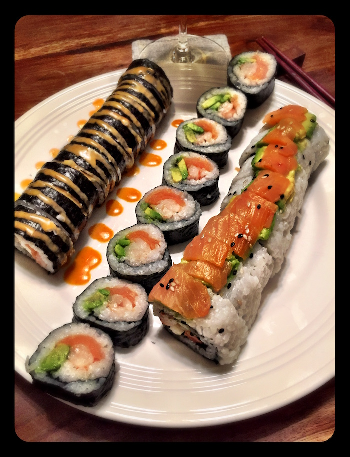 different types of sushi with salmon arranged on white plate shrimp tempura roll drizzled with different types of sauce