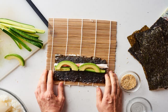 dragon roll sushi nori sheet avocado rice spread out on bamboo rolling mat placed on white surface