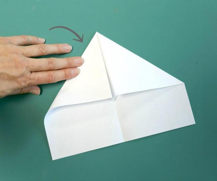 folding a piece of white paper on turquoise background paper airplane instructions diy tutorial step by step