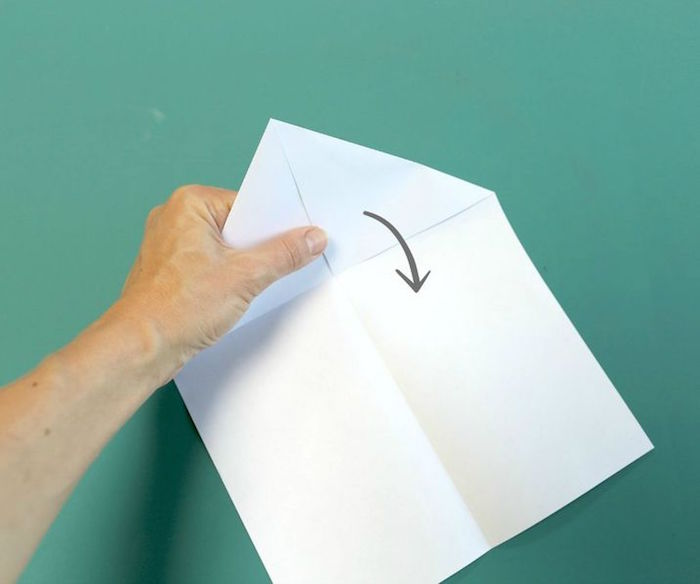 folding a white piece of paper to turn into a plane how to make a paper airplane easy diy tutorial