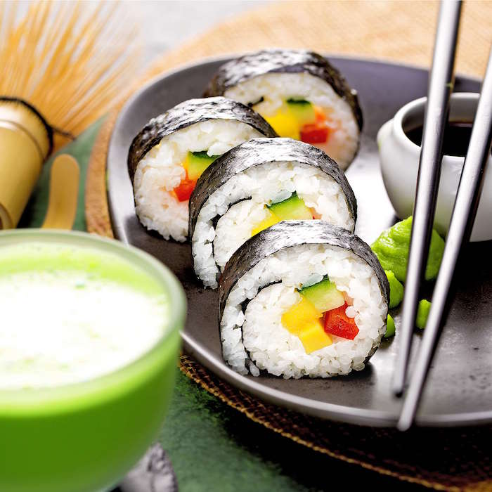 four sushi rolls with nori rice mango avocado arranged on black plate how to make sushi soy sauce black chopsticks on the side
