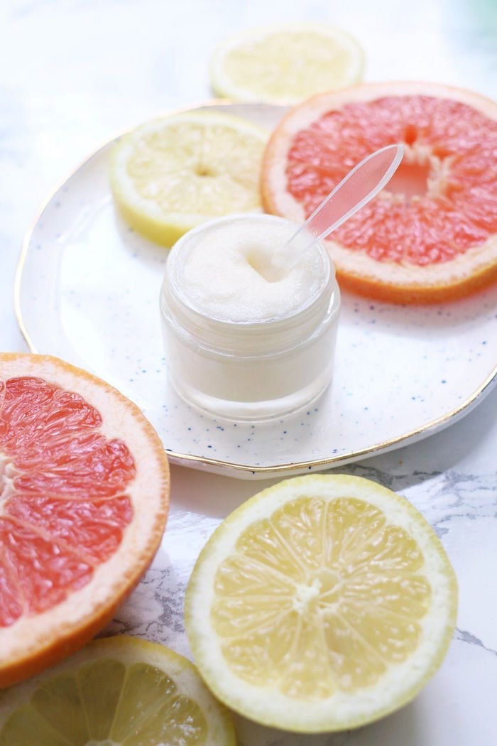 grapefruit and lemon sliced on marble surface with ceramic plate how to use lip scrub plastic container with lip scrub