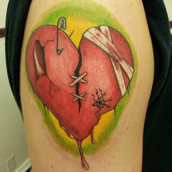 green background on red heart broken with stitches safety pin bandages heart tattoo on chest shoulder tattoo
