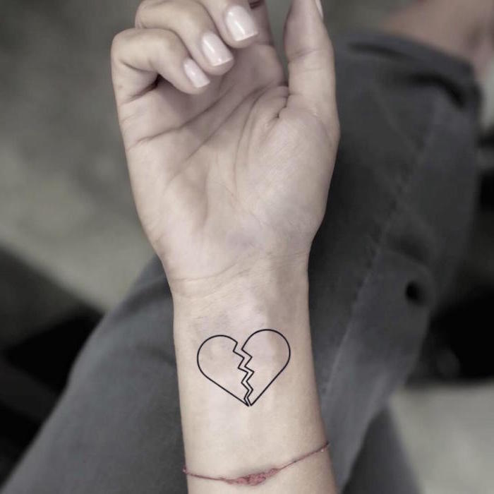 heart tattoo on hand black outlines of heart broken in the middle wrist tattoo on woman wearing red thread as bracelet